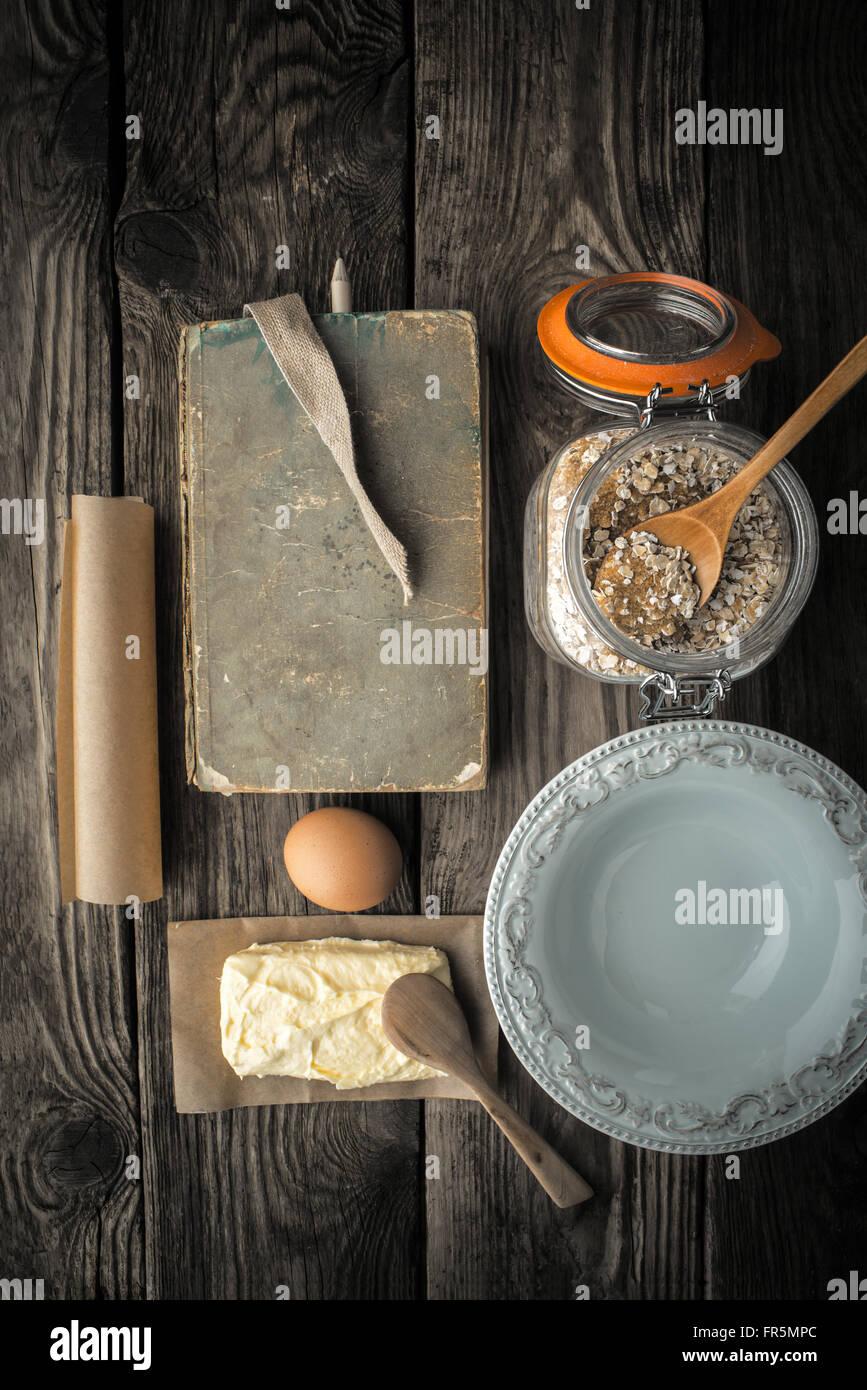 Livre de recettes, plaque et ingrédients pour les cookies sur une table en bois super vertical still life Photo Stock