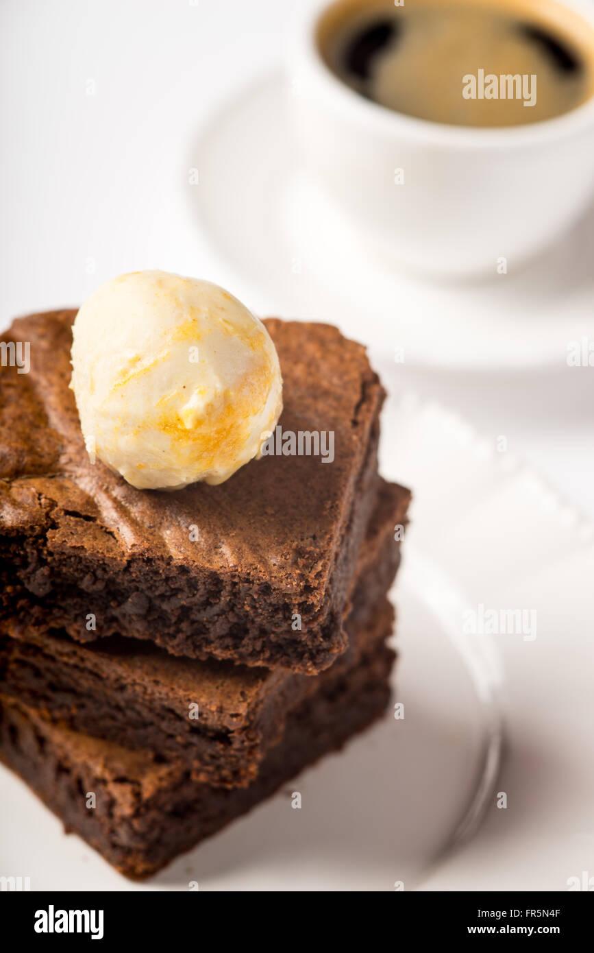 Brownie avec de la crème glacée et une tasse de café sur la table verticale Photo Stock