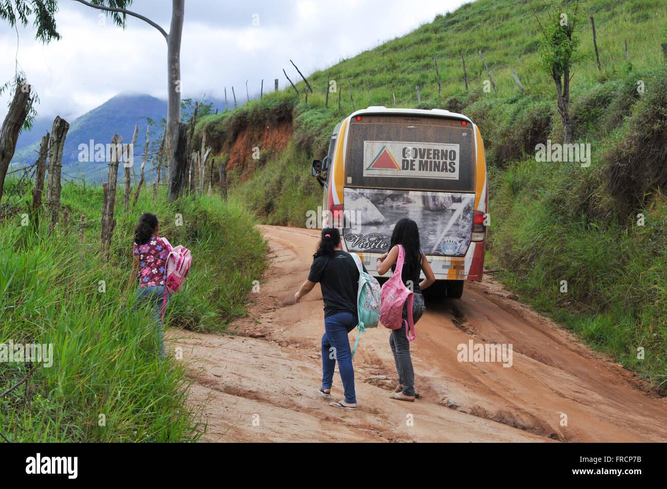 Les adolescents et les transports scolaires route de terre dans la campagne Banque D'Images
