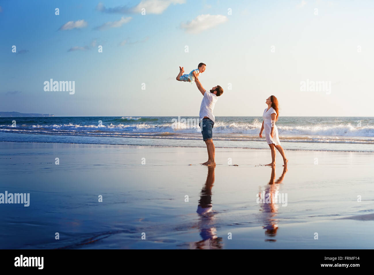 Happy Family - père, mère, fils bébé marche avec plaisir le long du bord de mer au coucher du soleil sur la plage Banque D'Images