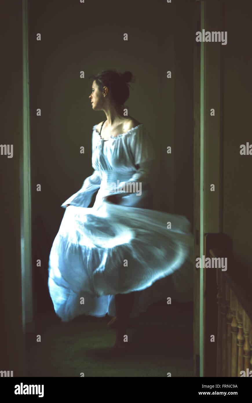 Jeune femme dansant dans une vieille maison longue robe romantique blanc Photo Stock
