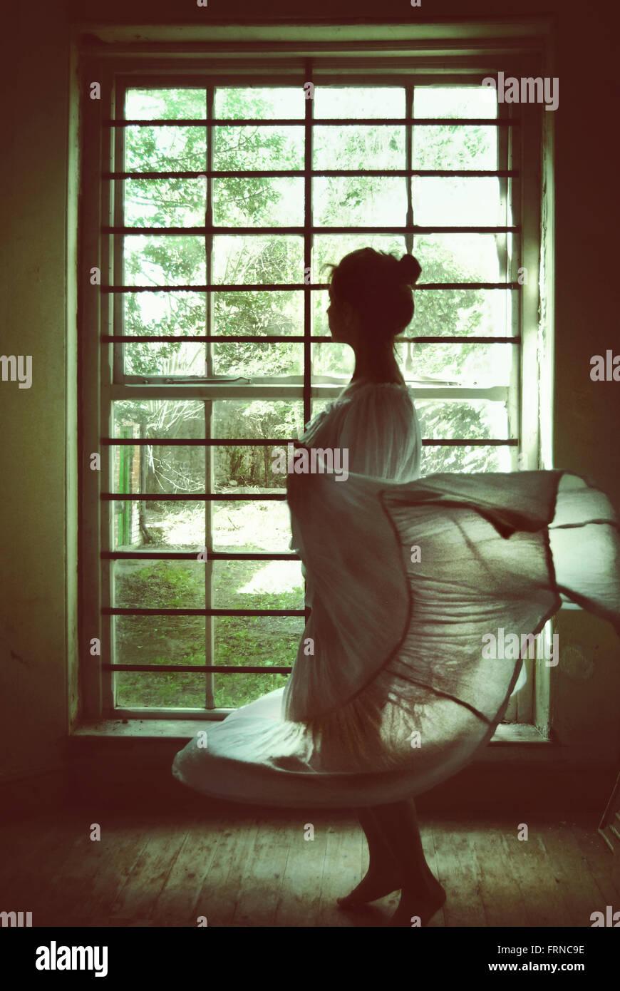 Jeune femme dansant dans une vieille maison avec une grande fenêtre Photo Stock