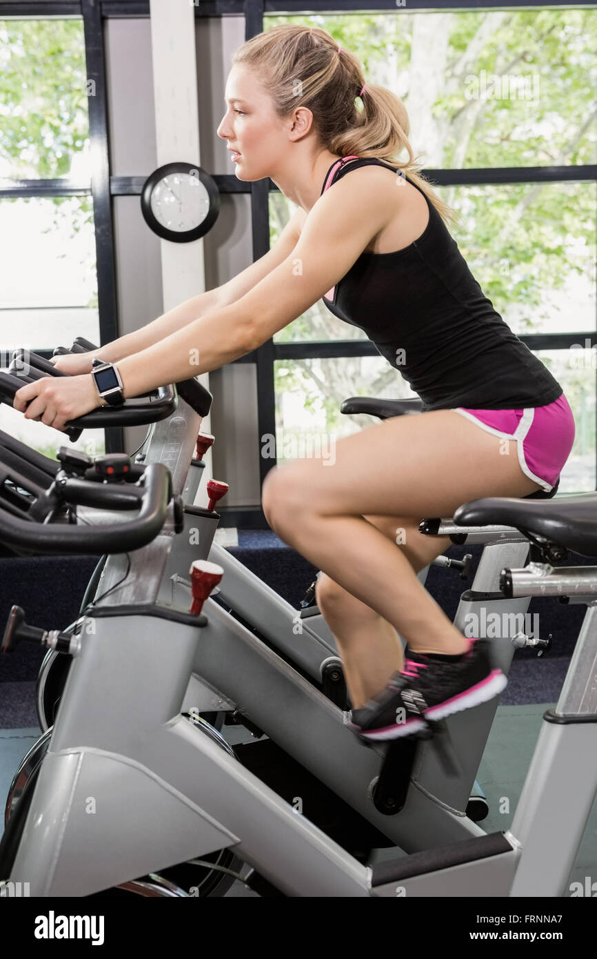 Woman on exercise bike Photo Stock