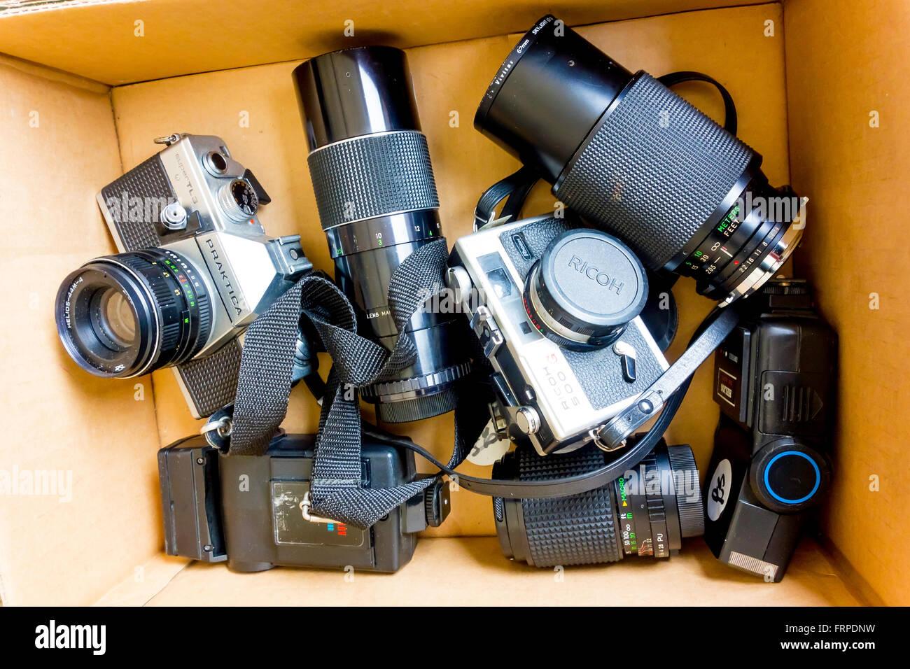 Une collection de vieux films 35mm numériques, d'objectifs et flashes pour vendre sur un marché aux puces, wc séparés. Banque D'Images