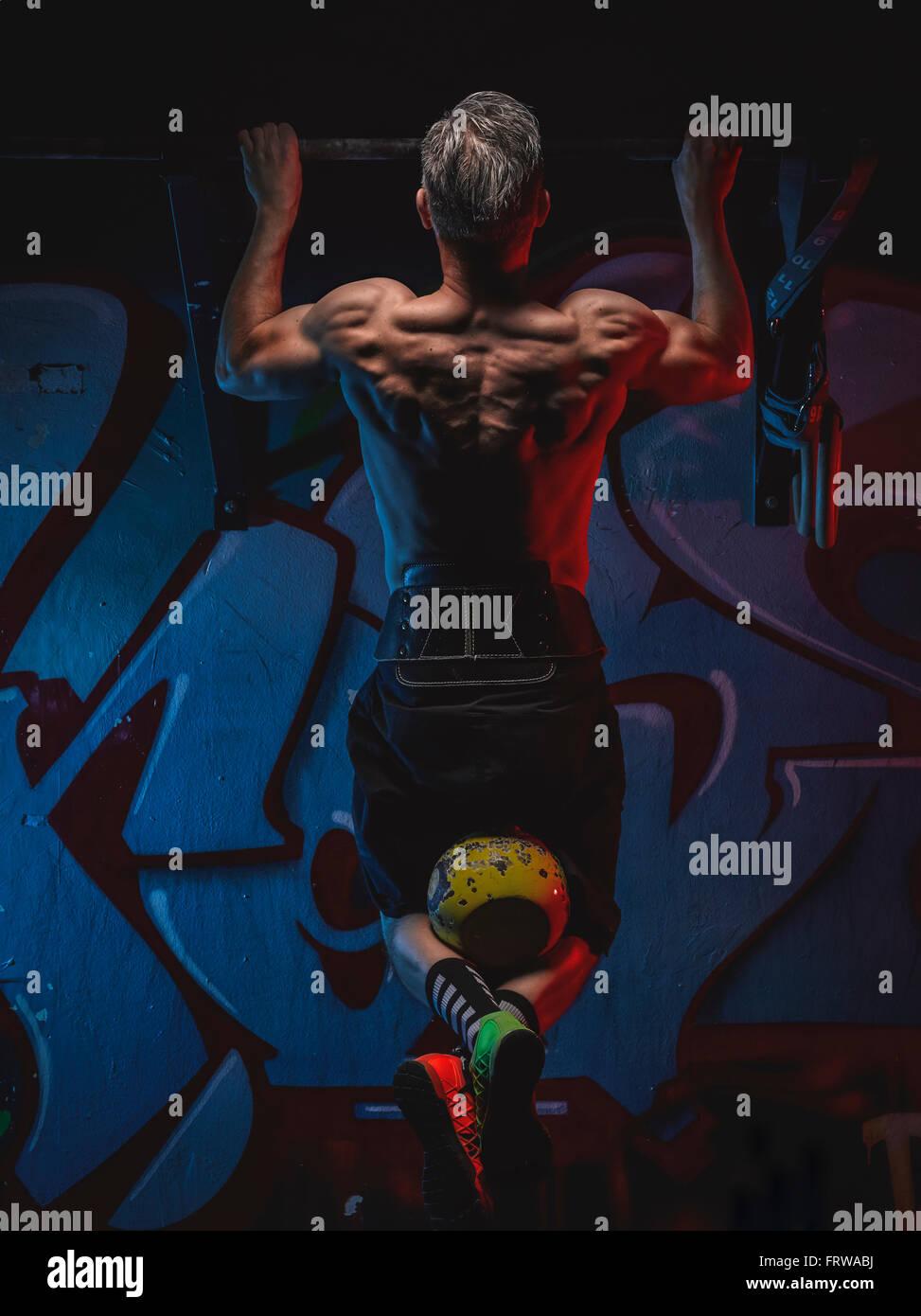 Athlète crossfit mature faisant chin-ups avec kettlebell Photo Stock