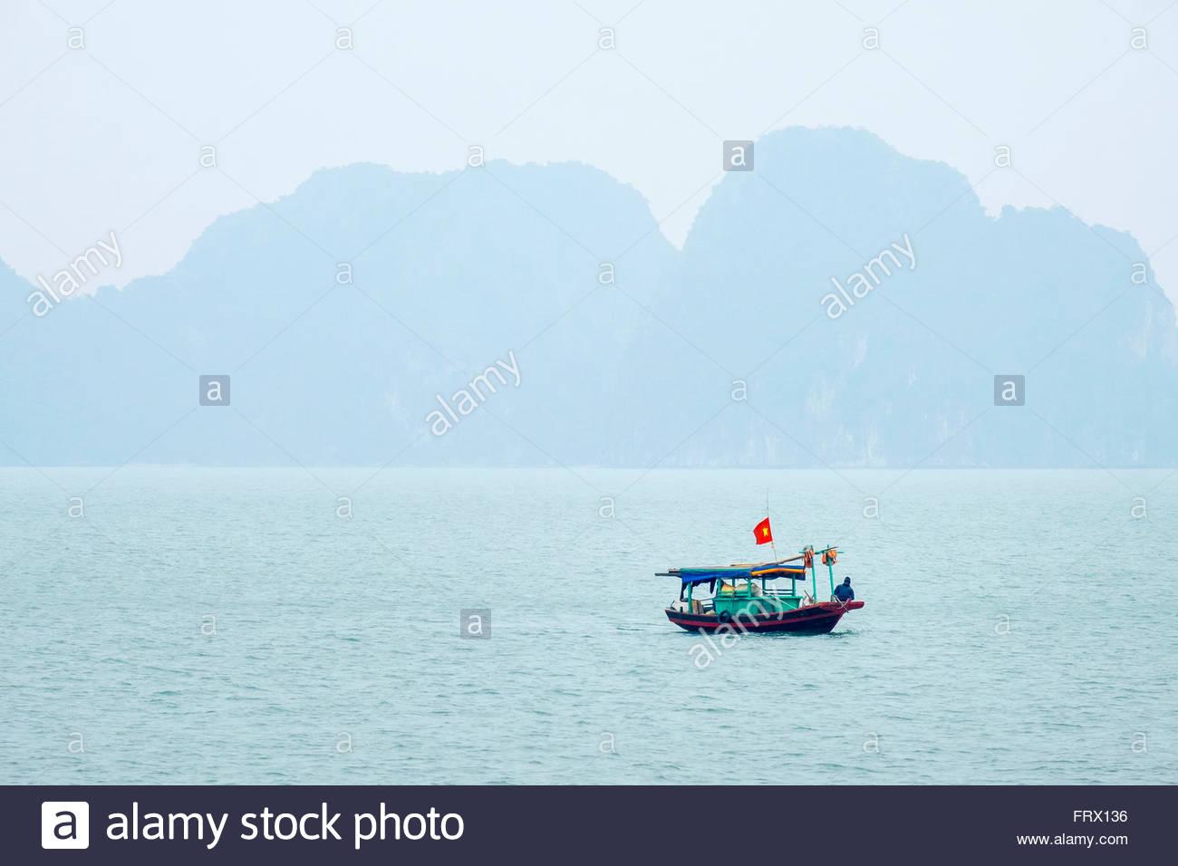 Petit bateau de pêche en baie d'Ha Long en un jour brumeux, Province de Quang Ninh, Vietnam Photo Stock