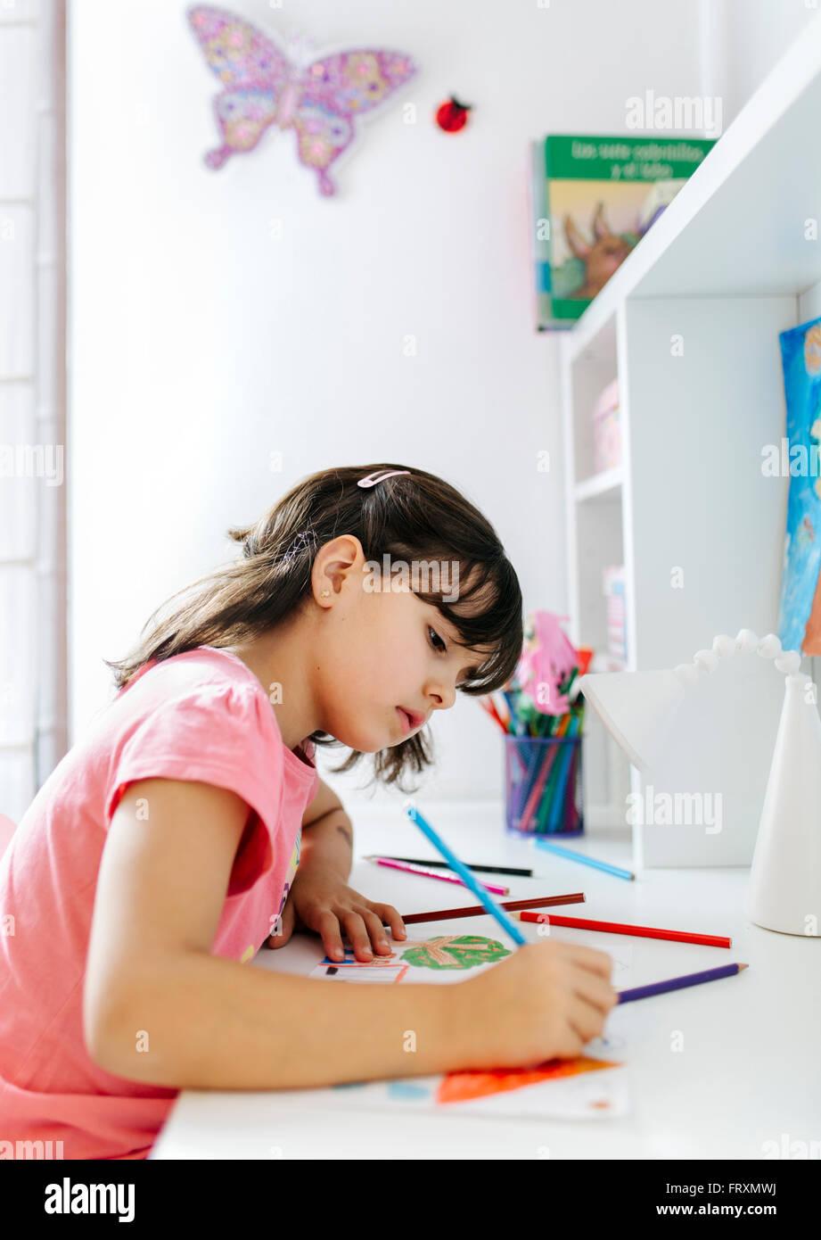 Petite fille s'appuyant sur son bureau à la maison Photo Stock