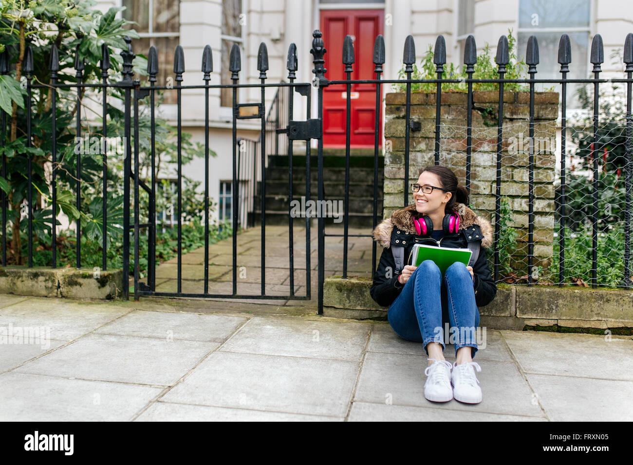 Londres, fille étudiante avec casque et pavé d'écriture Photo Stock