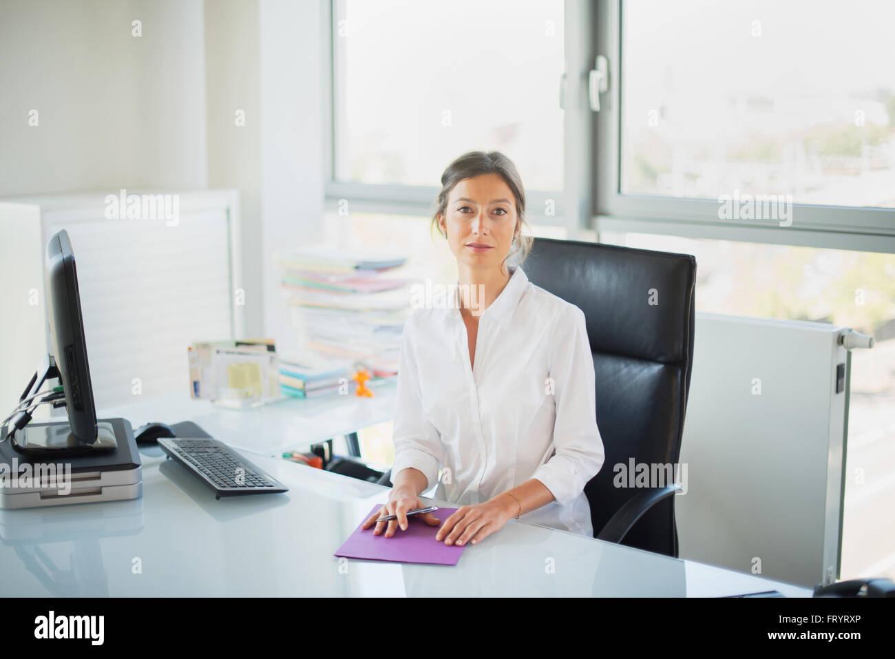 Femme manager looking at camera dans son bureau blanc femme assise