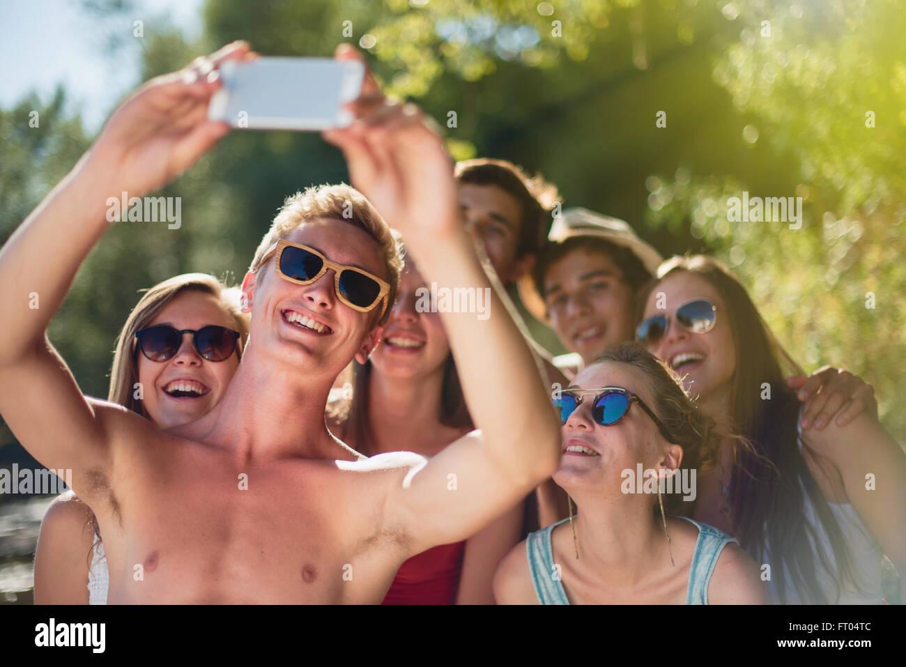 Se concentrer sur les jeunes gens en tenant vos autoportraits sur un  smartphone et posant bras 6ac5637d98c