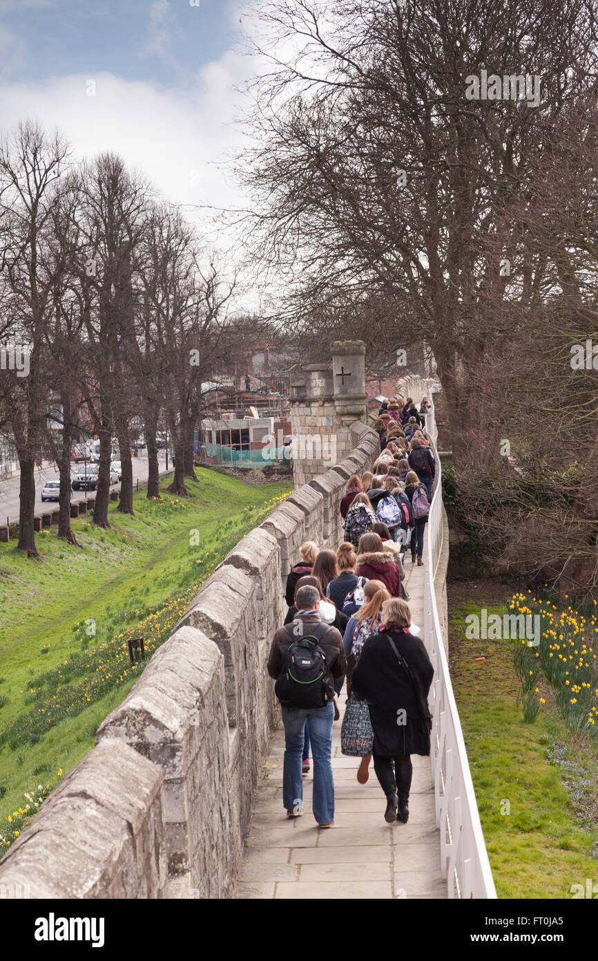 Étudiants et enseignants à pied le long des murs de la ville de York, North Yorkshire, Angleterre, Royaume Photo Stock