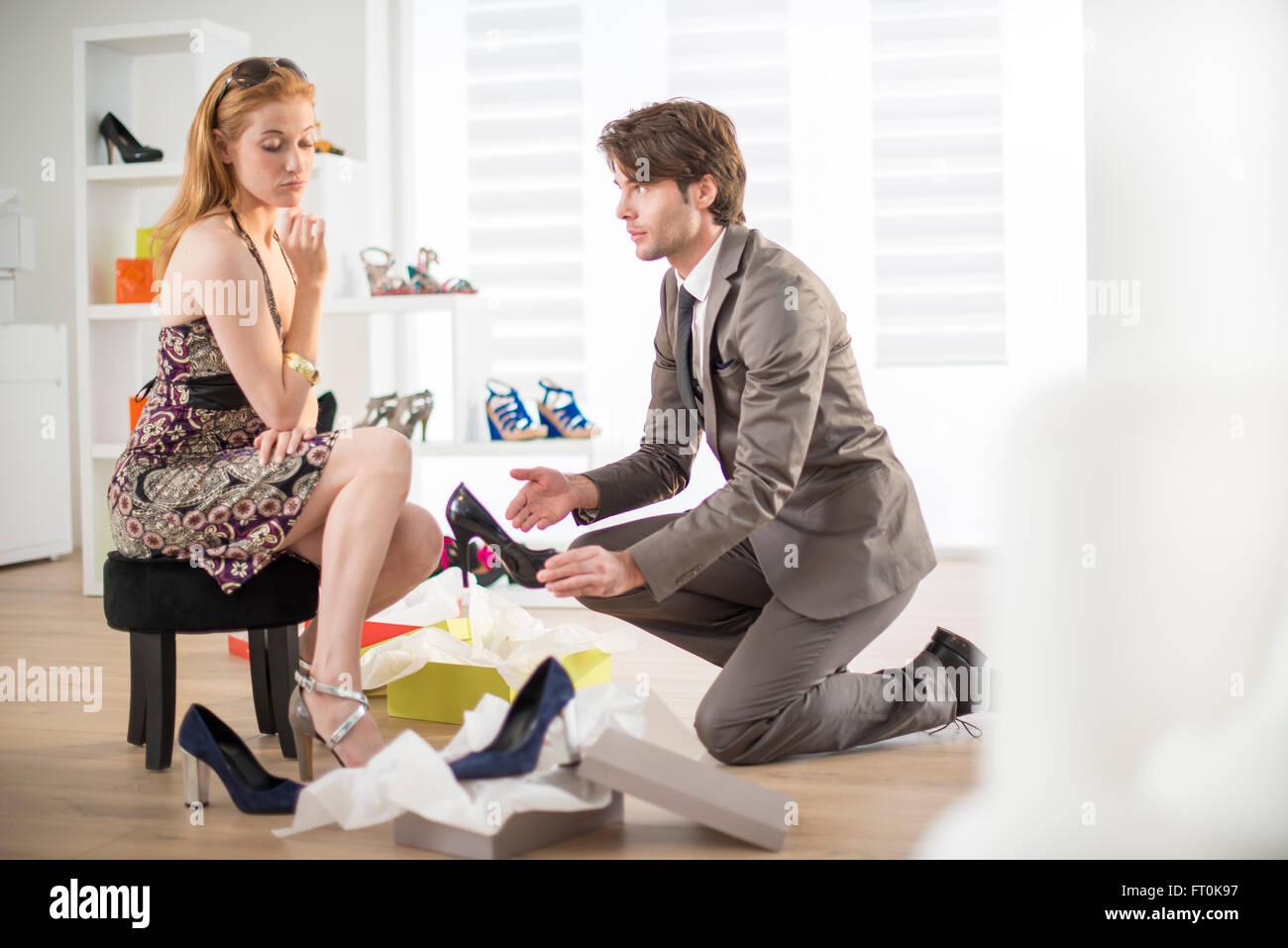93ce0b77dea79f Le vendeur propose d'essayer des chaussures d'une cliente Banque D ...