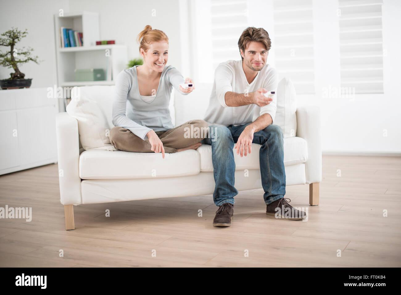Cheerful couple jouer au jeu vidéo sur un canapé Photo Stock