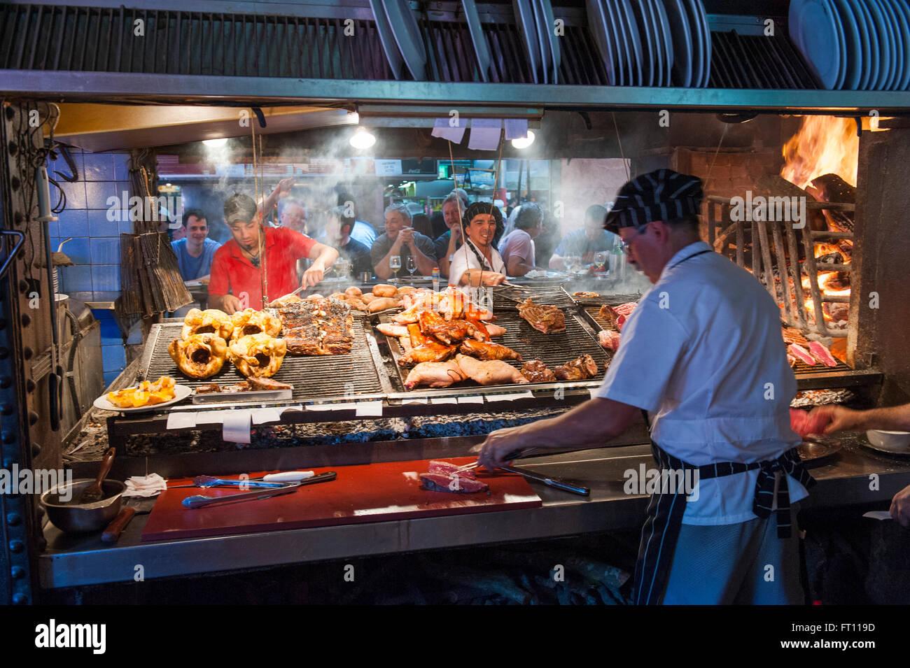 La préparation des cuisiniers et de la viande de boeuf, type Parilla restaurant, Mercado del Puerto, Montevideo, Photo Stock