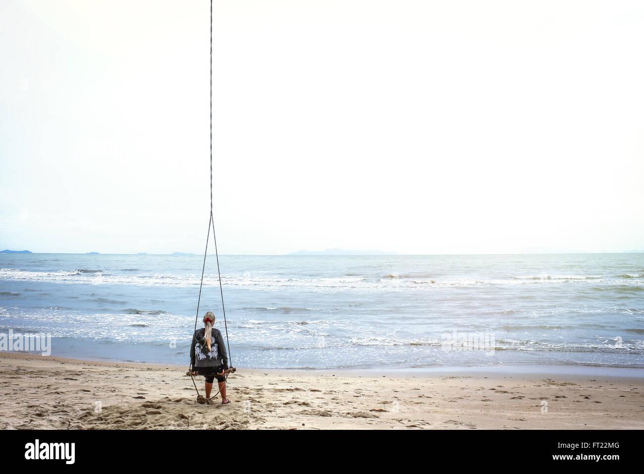 Femme pensive sur la plage à la recherche dans la distance Photo Stock