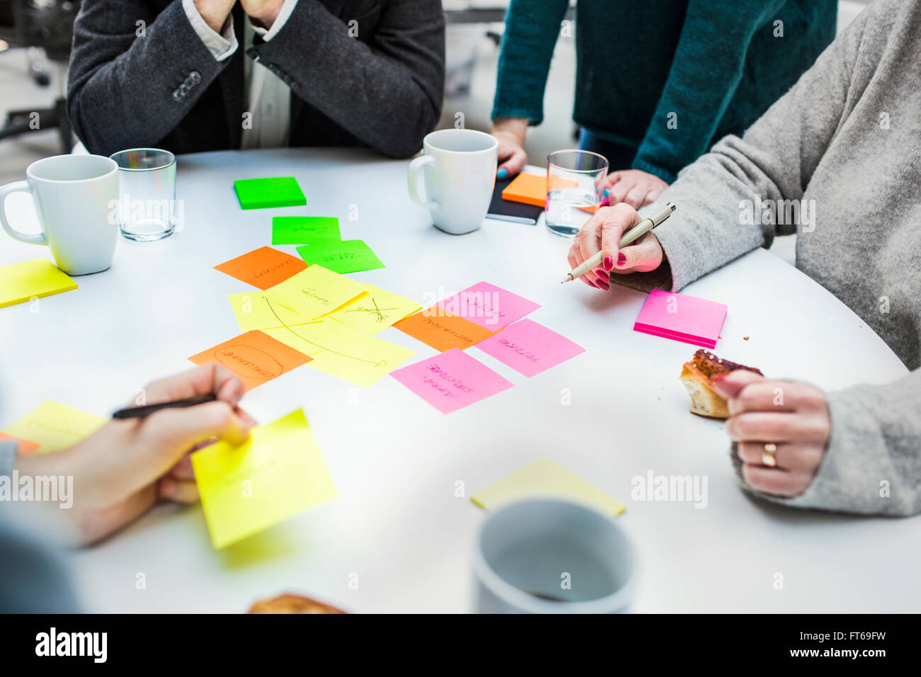 Portrait des gens d'affaires avec des notes adhésives à table dans creative office Photo Stock