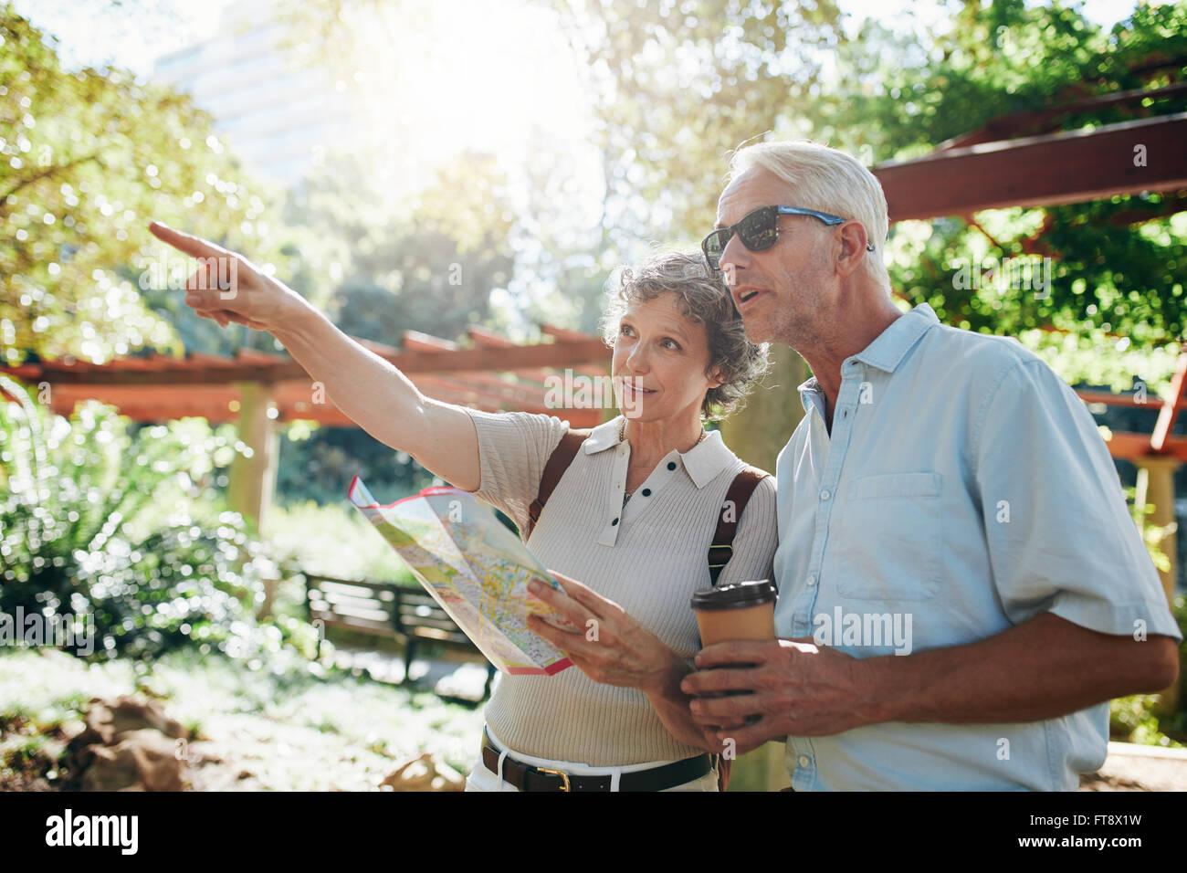 Couple de touristes à l'aide d'un guide de la ville et vers les emplacements de recherche Photo Stock