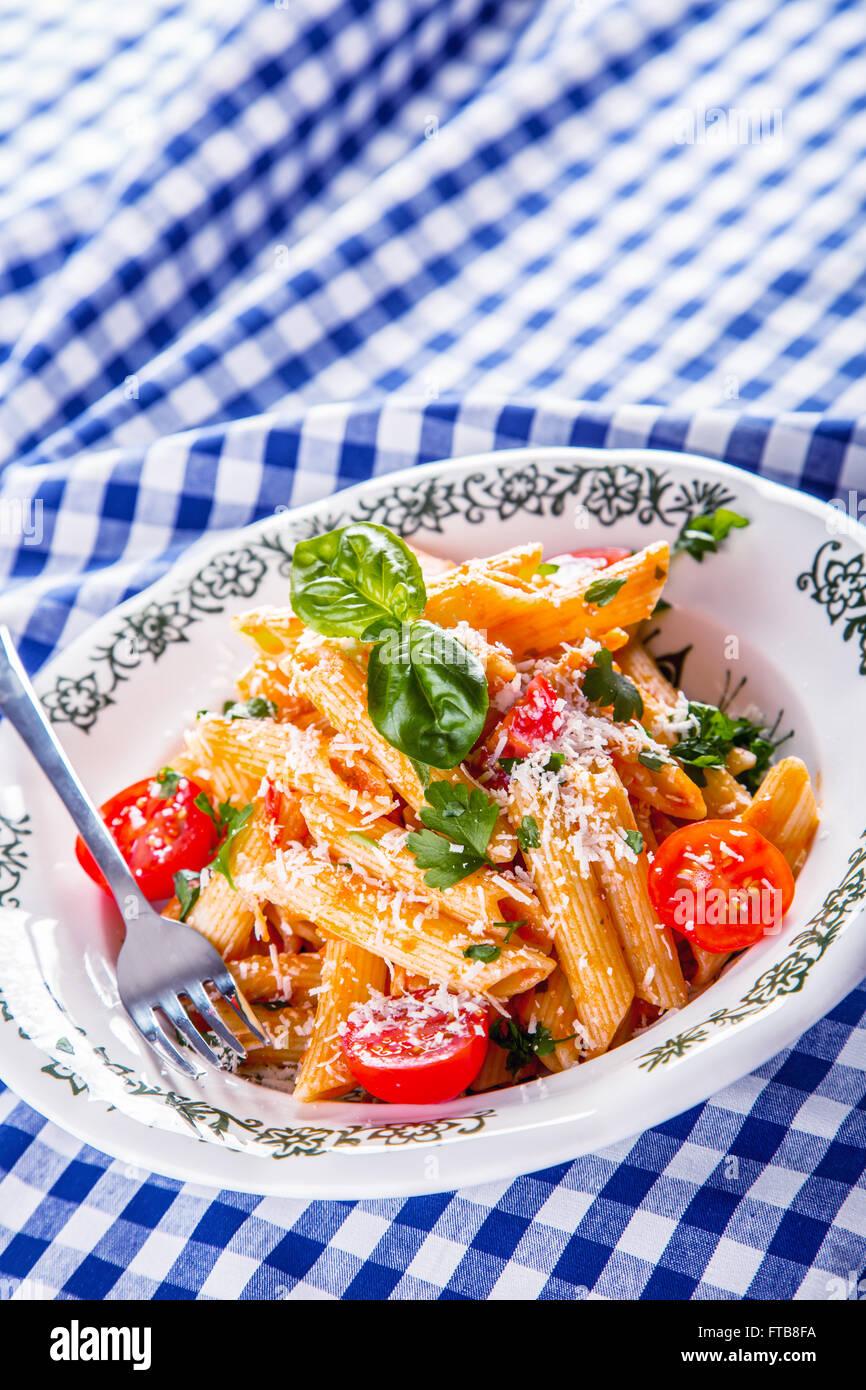 Plaque avec pene pâtes sauce bolognaise tomates cerise haut de persil et les feuilles de basilic sur nappe Photo Stock