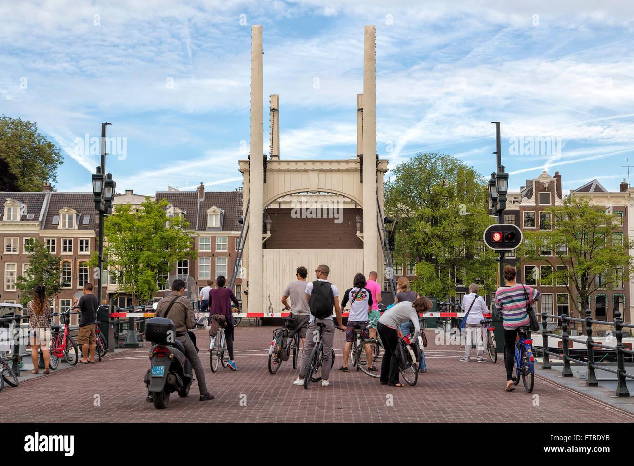 Personnes debout avec des vélos sur le pont au-dessus du canal à Amsterdam, Pays-Bas Banque D'Images