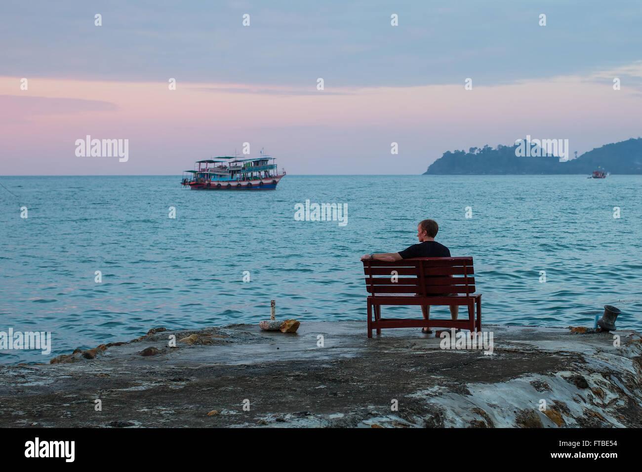 Homme seul est assis sur un banc sur la côte face à la mer. Photo Stock