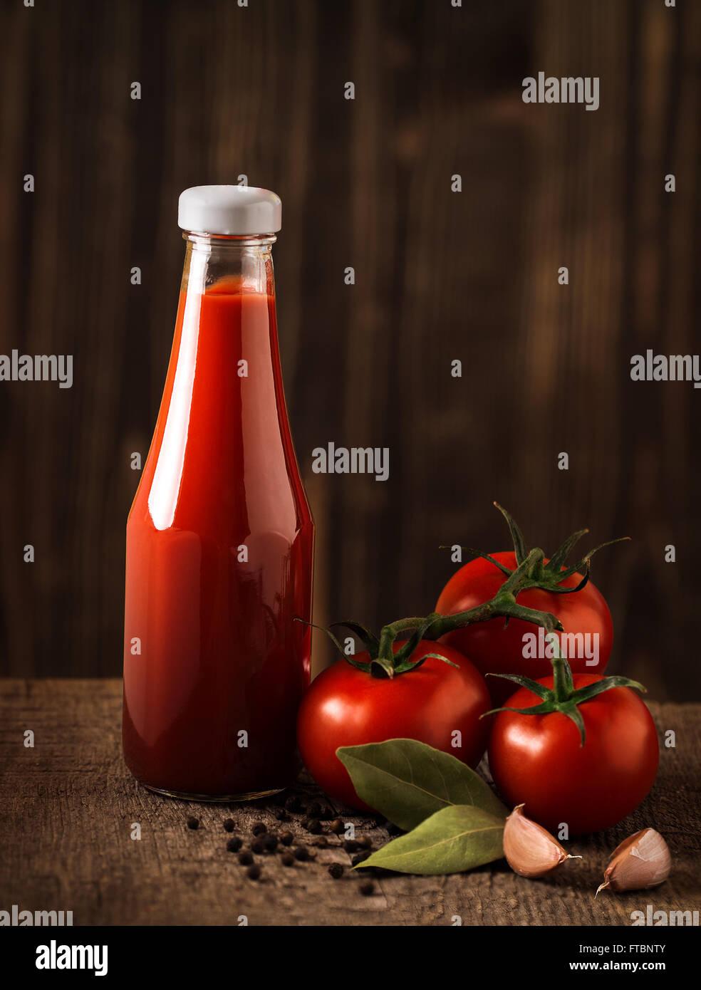 La vie encore sombre avec le ketchup et les ingrédients sur les bois brut Photo Stock