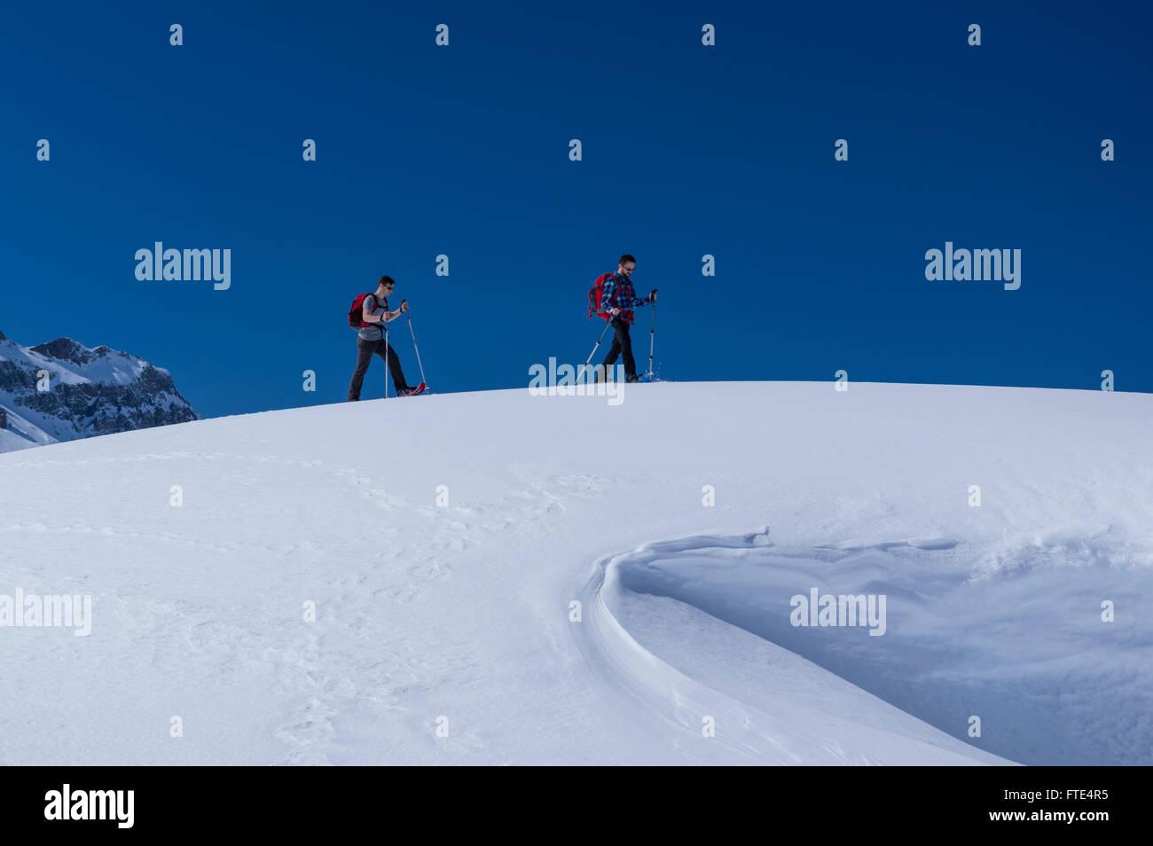 Deux randonneurs en raquettes homme randonnée sur un jour d'hiver ensoleillé dans les Alpes suisses. Photo Stock