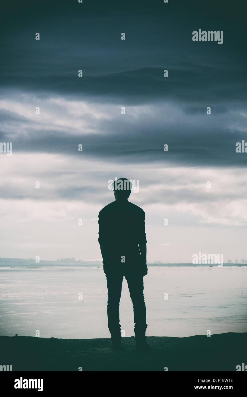 Homme debout près de la rivière Photo Stock