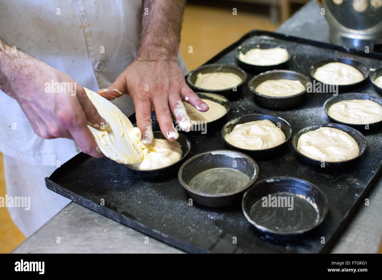 Baker de faire des pâtisseries dans une boulangerie de métal de remplissage des boîtes de four sur Photo Stock