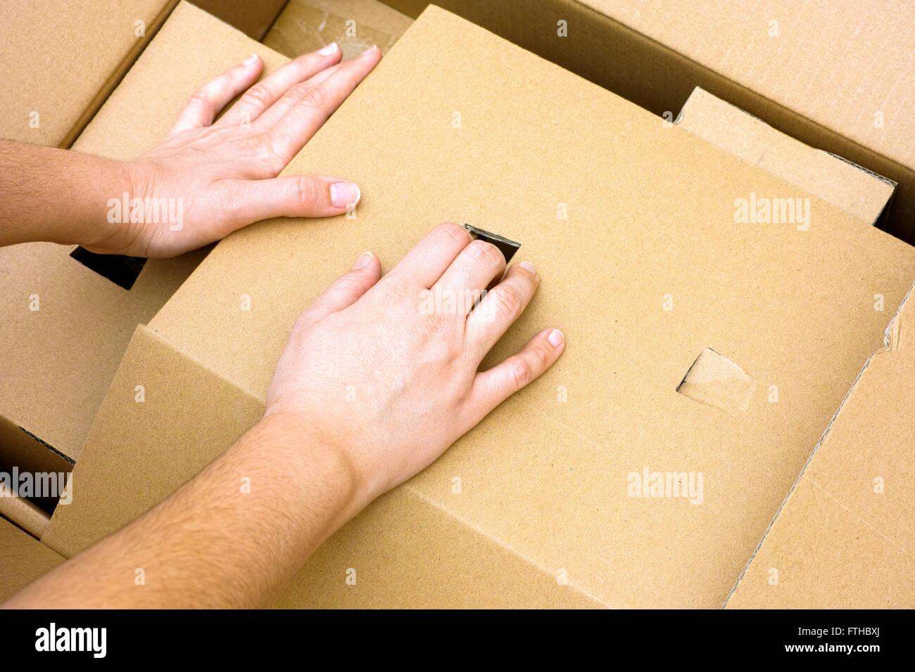 Mains femme gros déballage du carton. Photo Stock