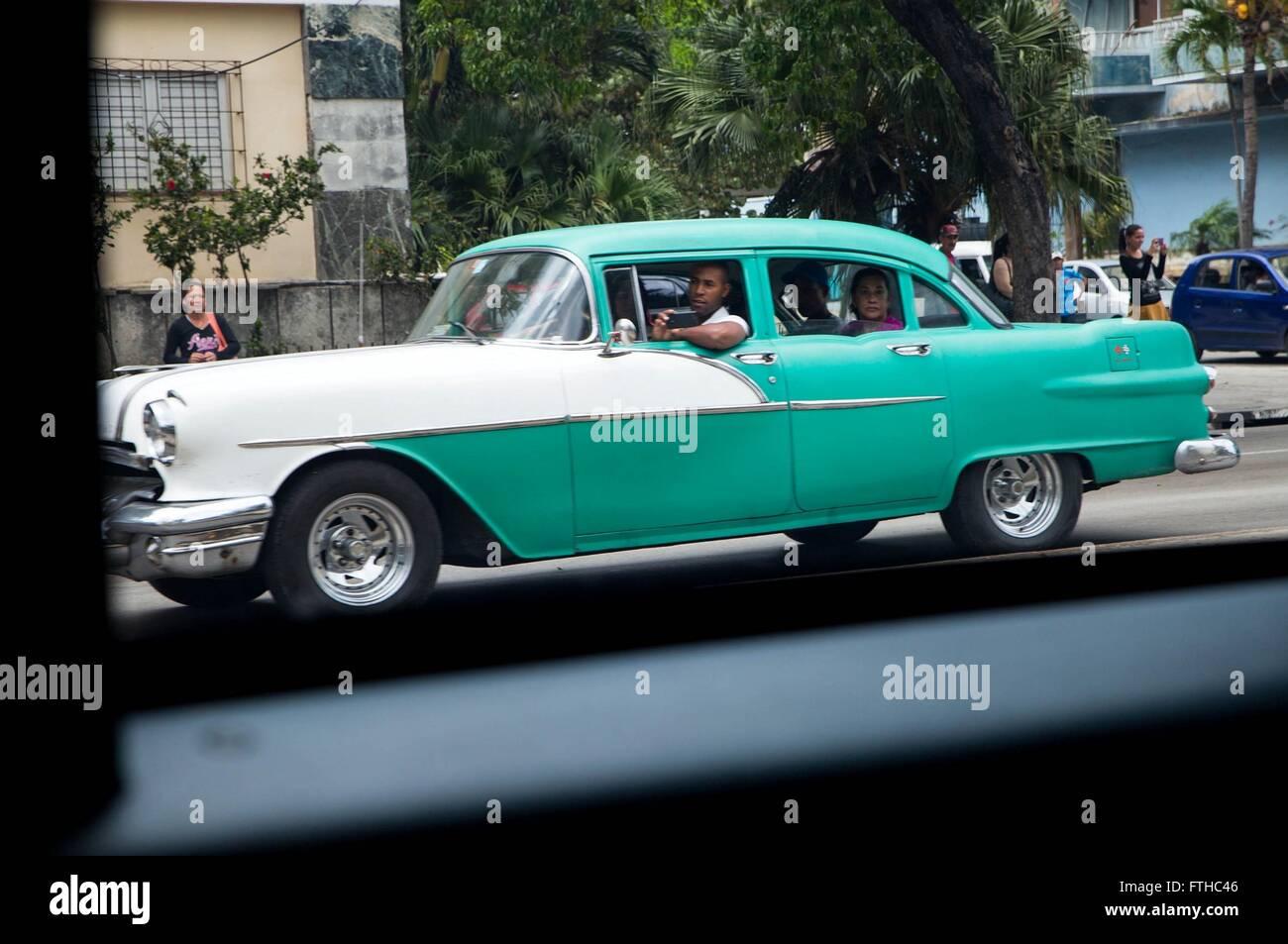 American Vintage une voiture conduite par une famille cubaine observe alors que le convoi du président américain Photo Stock