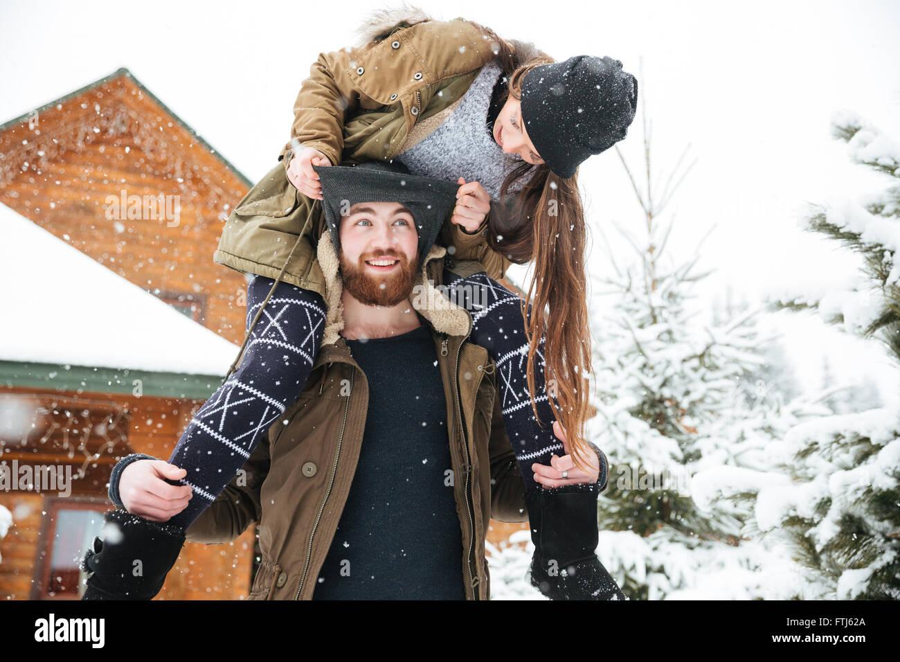 Belle jeune femme assise sur les épaules de l'homme et de s'amuser en hiver Banque D'Images