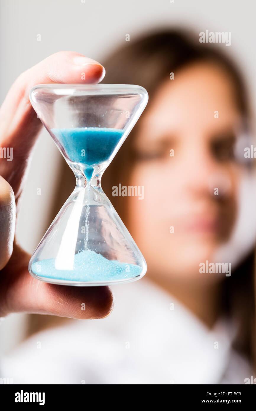 Avec un sablier sable bleu clair qui s'est tenu par une femme (floue) inquiète de fois qui passe Banque D'Images