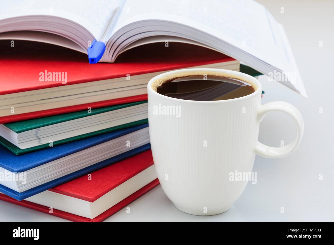 Scène d'études de l'étudiant avec des tas de livres sur un bureau avec une grande tasse de Photo Stock
