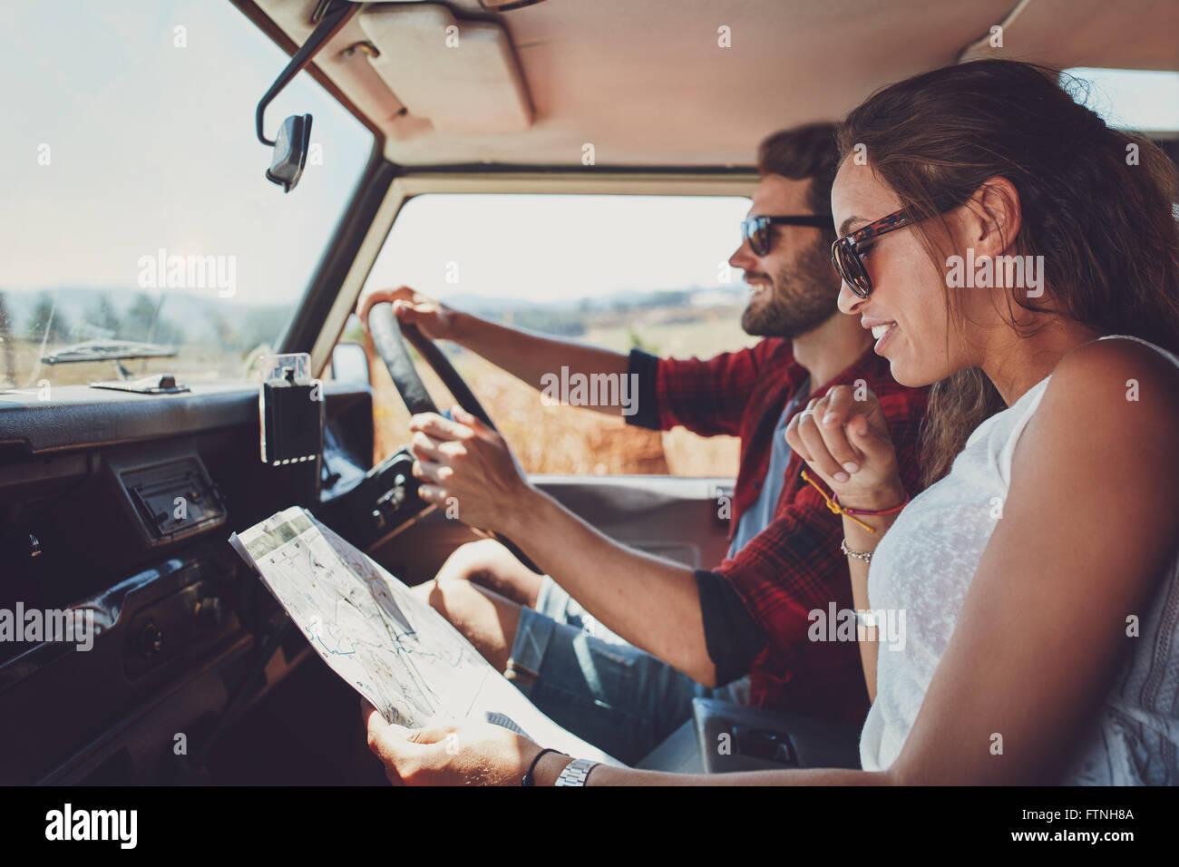 Vue latérale du jeune couple à l'aide d'une carte sur un roadtrip pour les directions. Young man and woman reading Banque D'Images