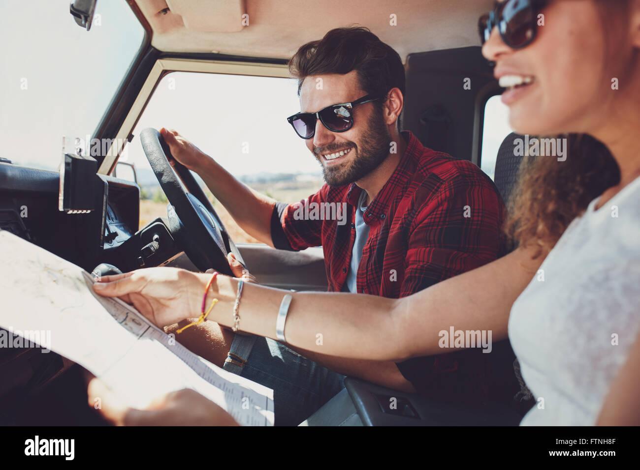 Jeune homme conduisant la voiture avec femme tenant une feuille de route. Jeune couple on road trip. Photo Stock