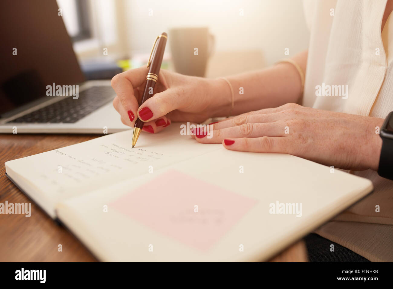 Close up image of woman writing notes dans son journal. Businesswoman assise à son bureau et prendre des notes Photo Stock