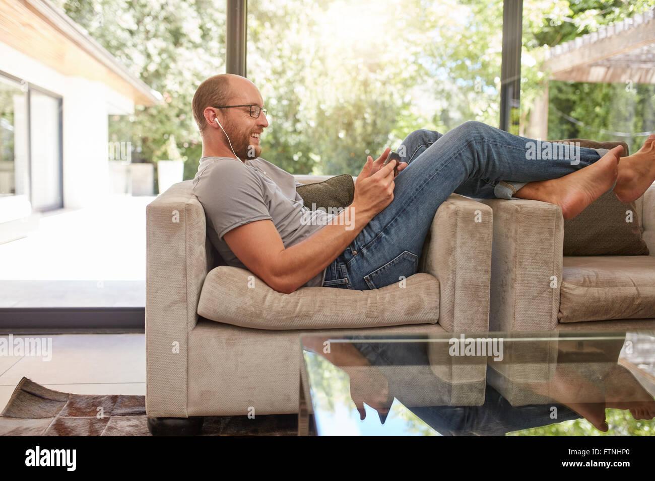 Vue côté droit d'un happy mature man using digital tablet, assis sur le canapé à la maison. Photo Stock