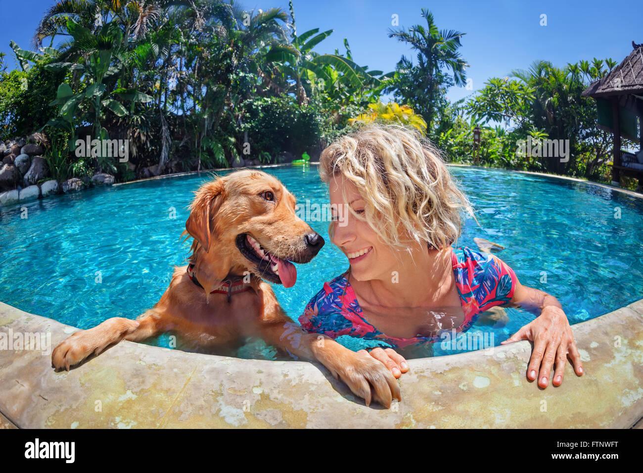 Portrait de femme smiley rigolo de jouer avec plaisir et de formation chiot golden retriever dans une piscine extérieure. Photo Stock