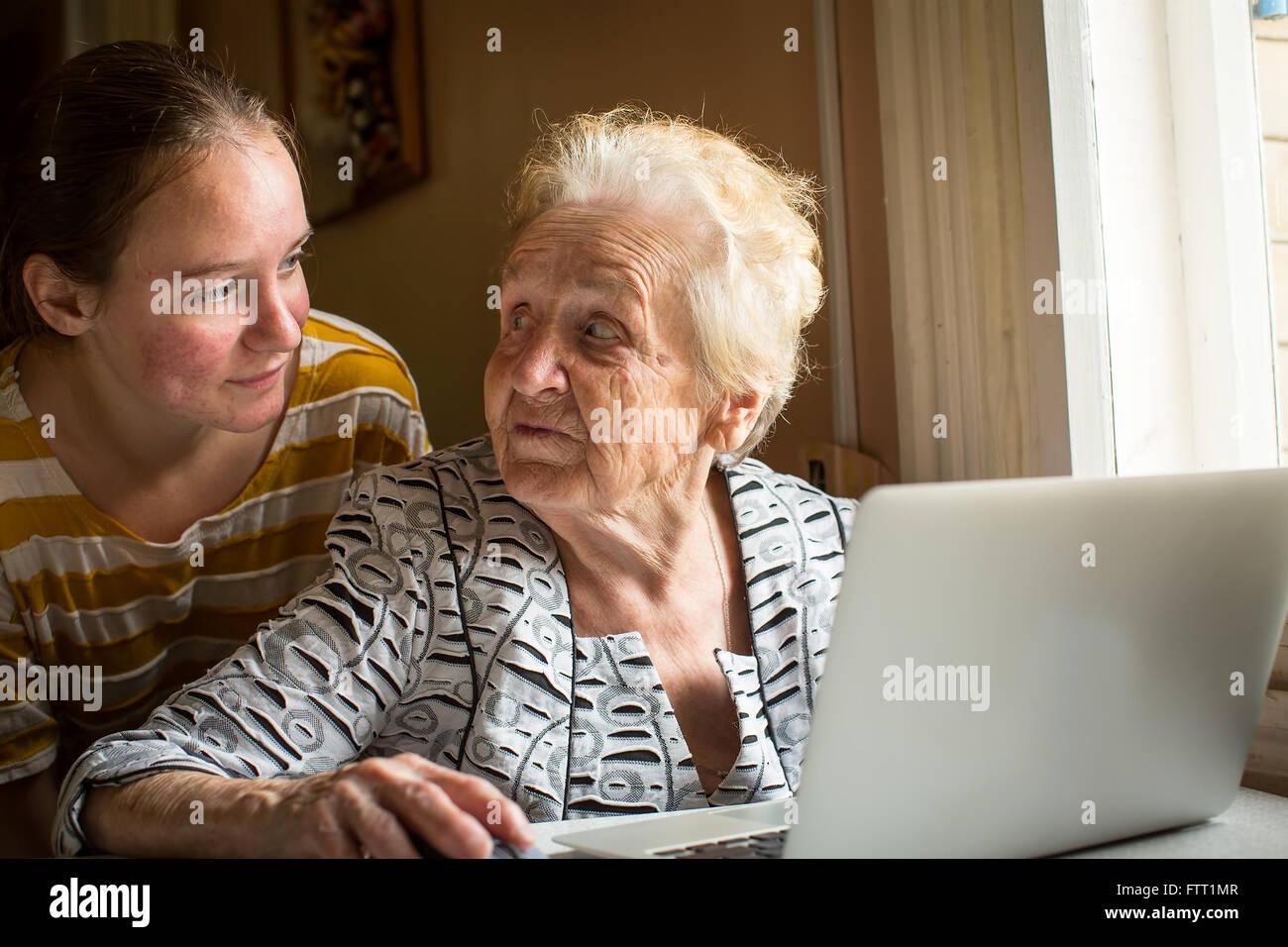 Jeune fille de sa grand-mère apprend à utiliser un ordinateur. Photo Stock