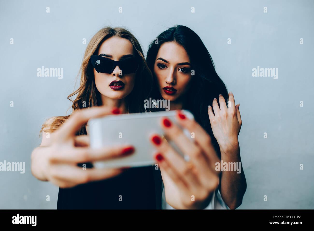 Deux copines en prenant un selfies Photo Stock