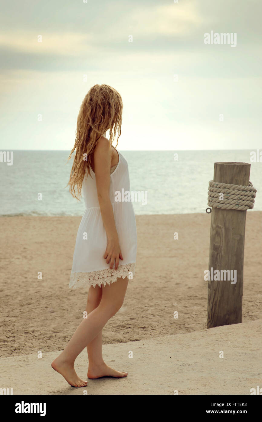 Blonde woman walking on beach Photo Stock