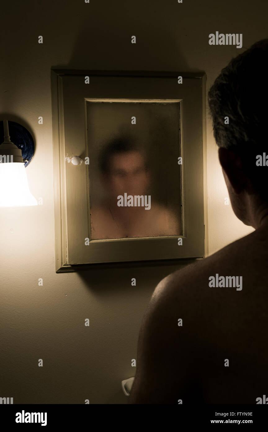 L'homme trouble confronte son image dans le miroir. Photo Stock