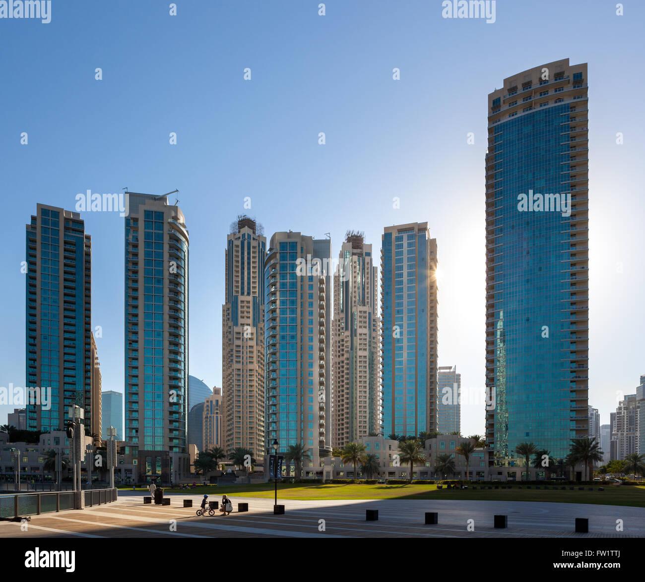Enfants jouant dans le parc en face de gratte-ciel dans le centre-ville de Dubaï. Photo Stock