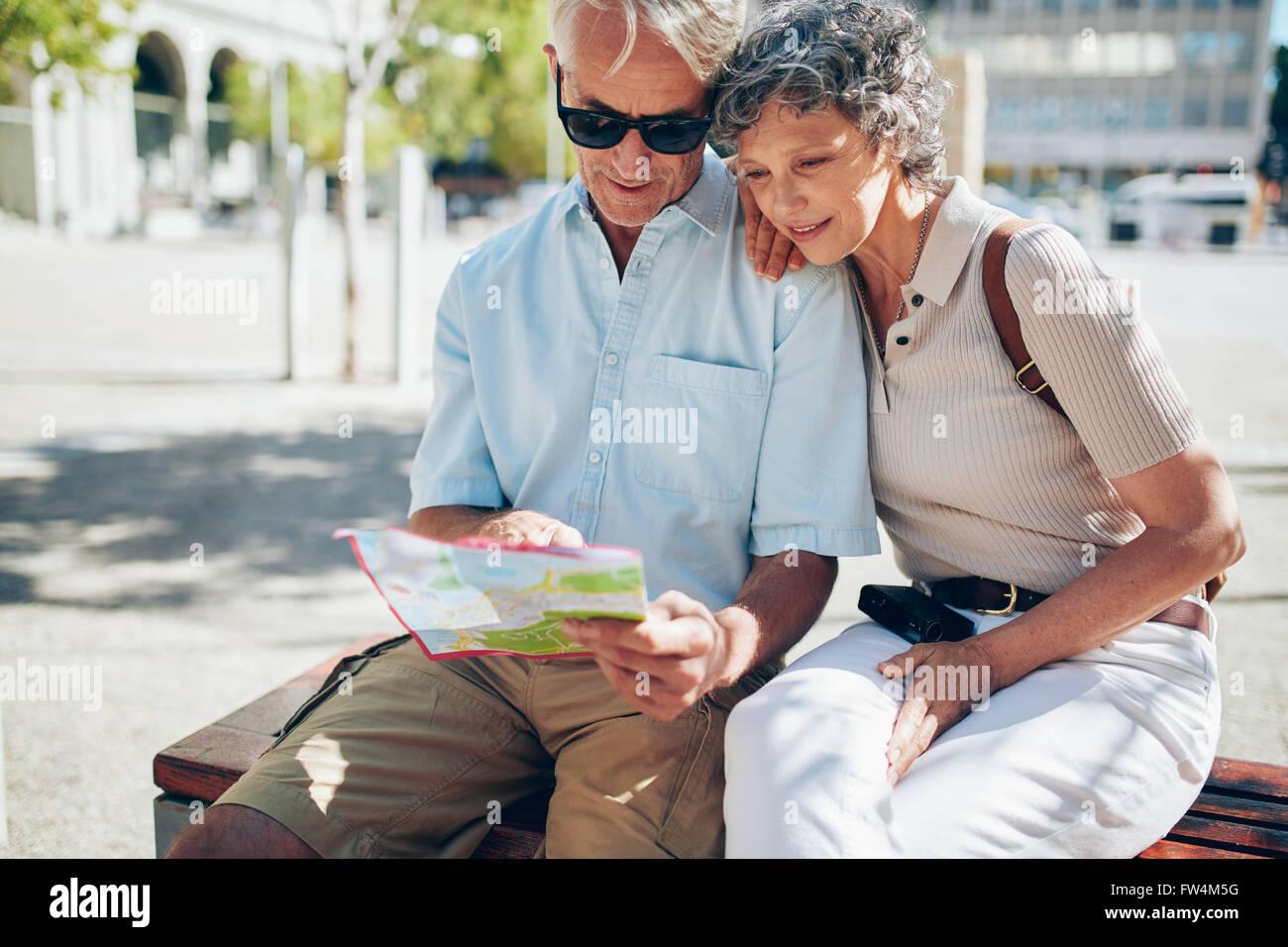Couple à la destination sur un plan de la ville. Deux aînés reading a map ensemble tout en restant Photo Stock