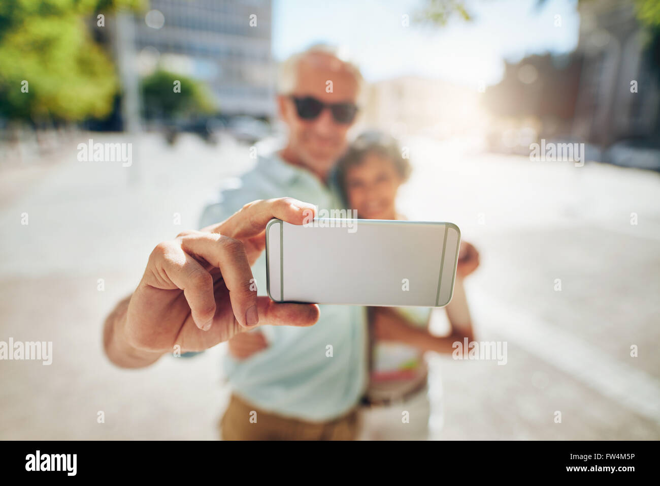 Happy senior couple embracing et prendre un autoportrait sur téléphone mobile à l'extérieur. En tourisme, l'accent Banque D'Images
