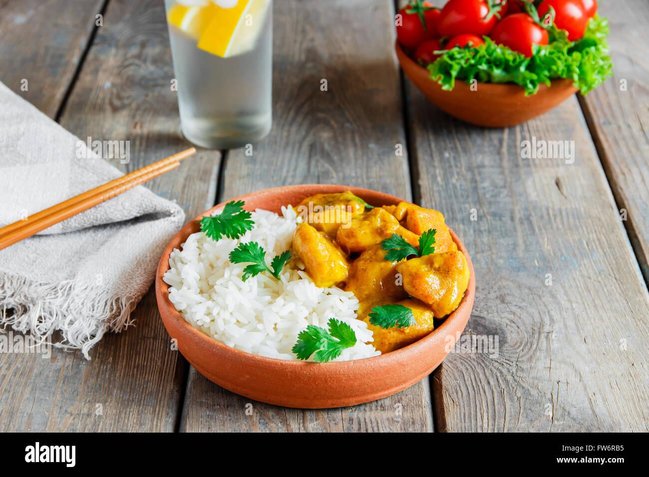 Poulet au curry avec du riz sur une surface en bois Photo Stock