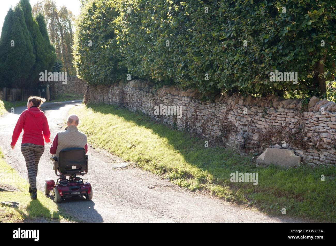 Vue arrière d'un homme âgé à l'aide d'un scooter de mobilité avec son soignant Photo Stock
