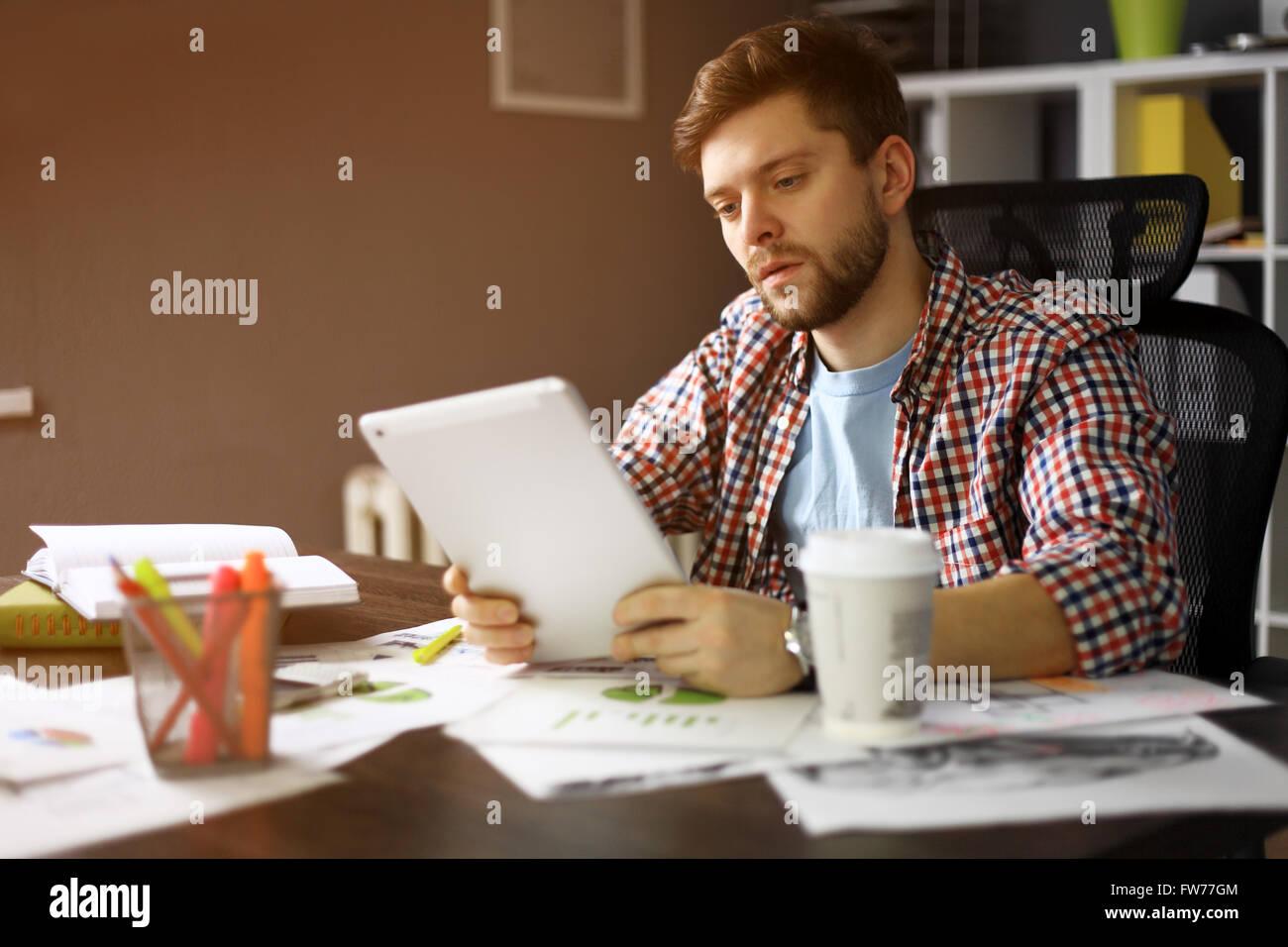 Homme sérieux personne regardant pour l'écran de tablette numérique tout en restant assis dans Photo Stock