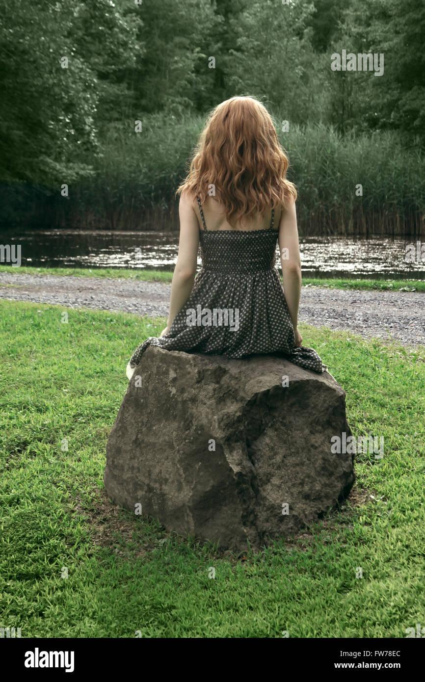 Vue arrière d'une jeune femme en robe à pois assis sur un rocher Photo Stock