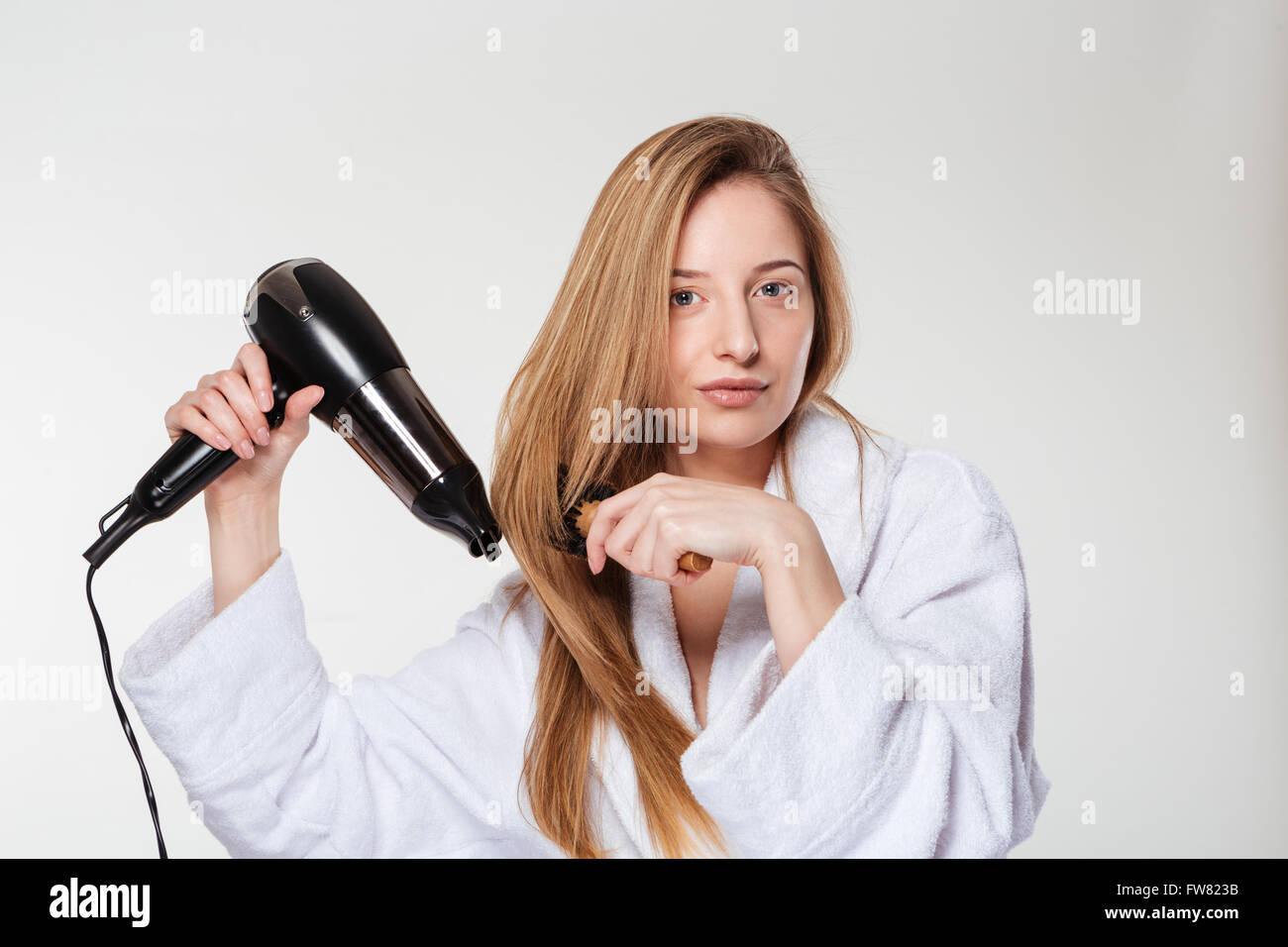 Jolie femme séchant ses cheveux isolé sur fond blanc Photo Stock